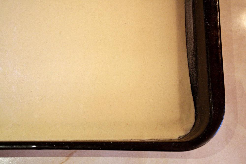 Слоеное тесто раскатываем и кладем на противень