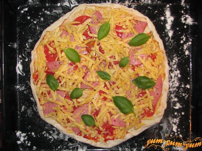 Смазываем тесто кетчупом, посыпаем сыром и ставим в разогретую духовку