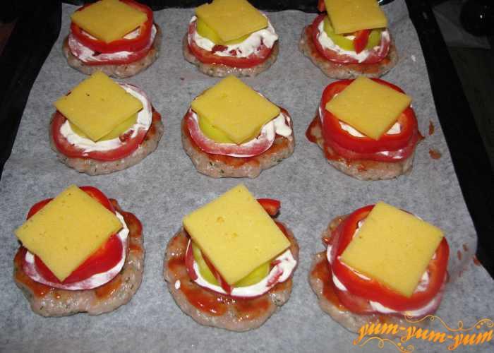 Украшаем котлеты кусочками сыра и ставим в духовку