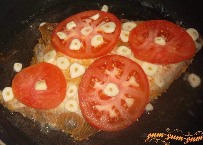 Сверху обжаренной рыбы выкладываем помидоры и чеснок