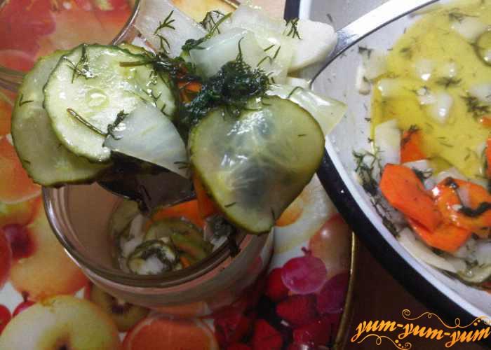 В чистые банки выкладываем горячий салат из огурцов