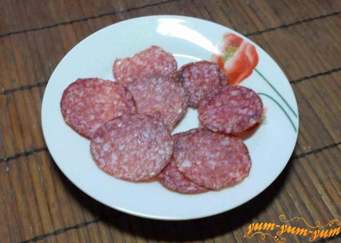 Копченую колбасу нарезаем тонкими колечками