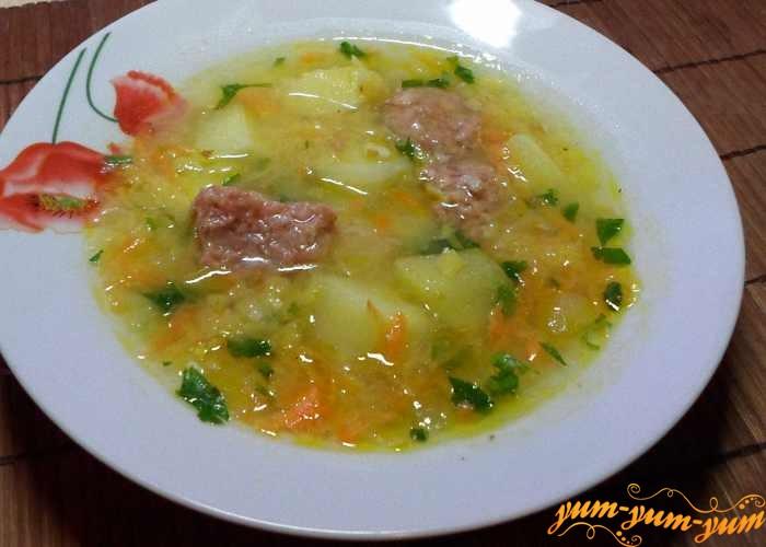 Выложить в суп тушенку и обжаренные на сковородке овощи – лук и морковь, готовить 10 минут.