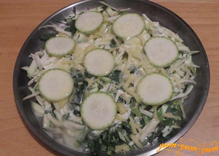 Поверх сыра выкладываем колечки кабачков