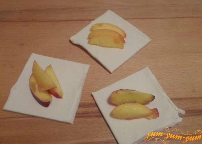 Кусочки персика окунуть в белок с пудрой и выложить на тесто