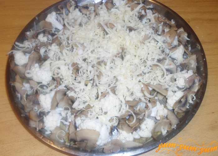 Натереть сыр на терке и посыпать им капусту с грибами