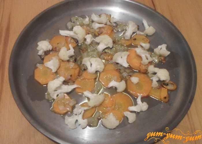 Сверху лука и моркови положить кусочки цветной капусты