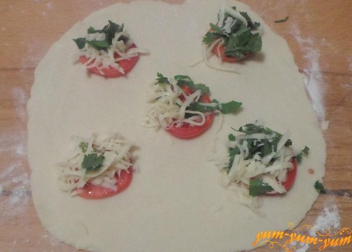 На раскатное тесто выложить кружочки помидоров с начинкой