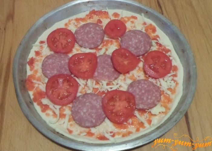 Положить кусочки помидоров рядом с колбасой