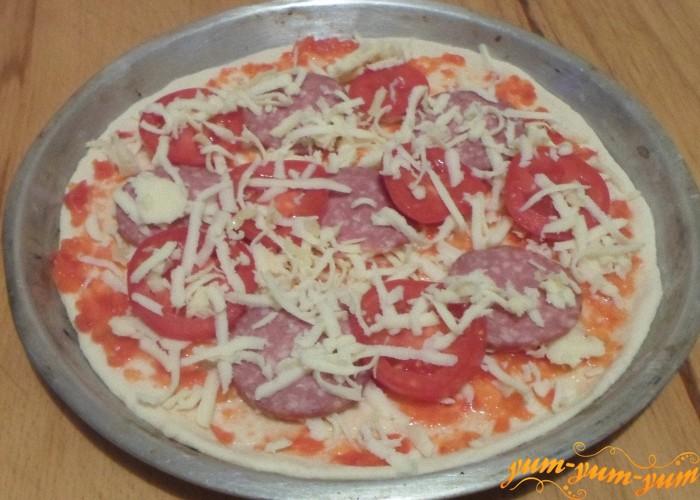 Посыпать оставшимся сыром и поставить пиццу в духовку