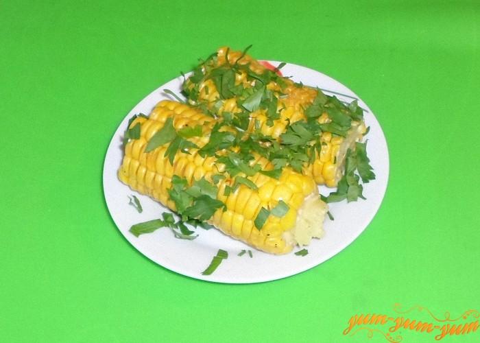 Кукурузу выложить на тарелку и посыпать со всех сторон смесью из зелени и соли