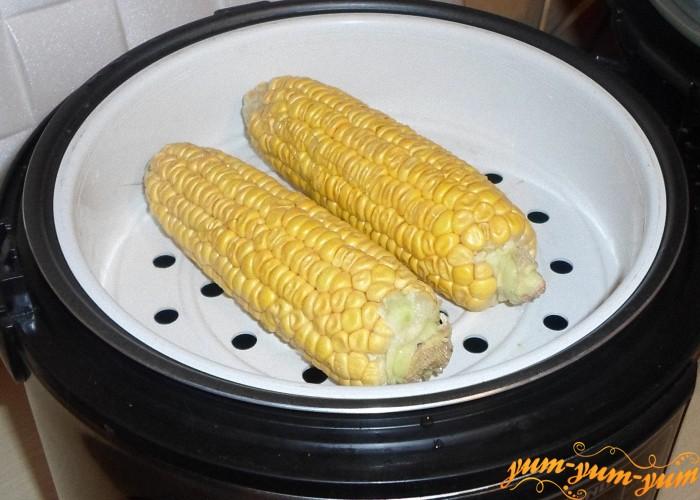 Поставить сверху чашу для варки на пару и выложить кукурузу
