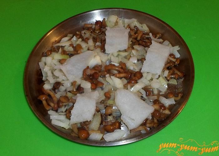 Кусочки рыбы выложить поверх грибов с луком