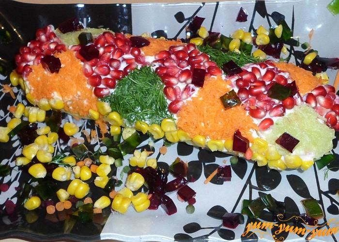 Посыпать поверхность салата подготовленными ингредиентами чтобы создать рисунок хлопушки