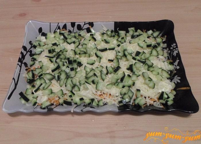 Свежий огурец нарезать мелкими кубиками и посыпать сверху сыра