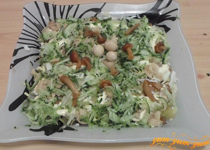 Верхний слой салата украсить мелко нарезанным свежим огурцом и маринованными грибочками