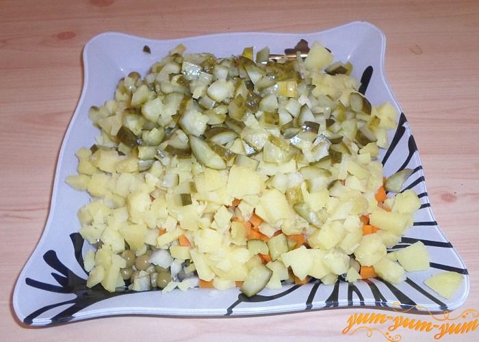 Картофель почистить и нарезать кубиками вместе с маринованными огурцами