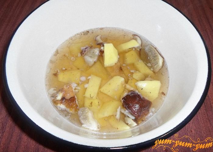 Картофель нарезать и добавить в кастрюлю к грибам