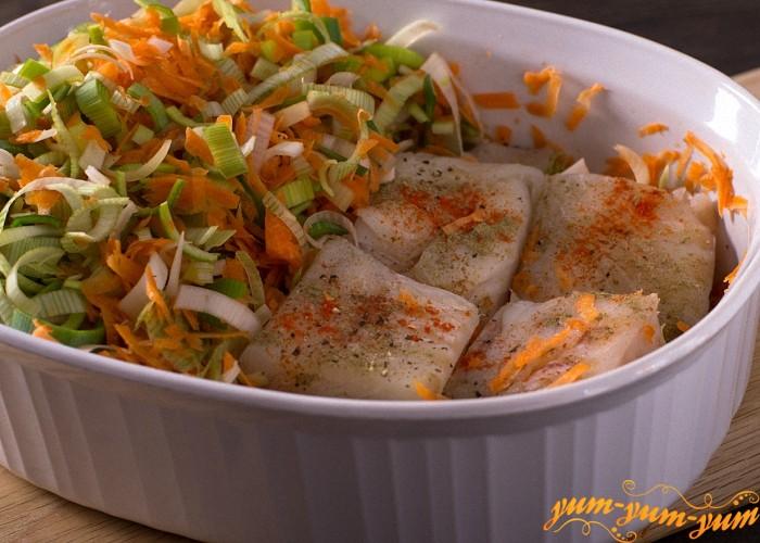 На рыбу выложить слой лука и слой моркови